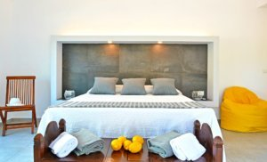 The bedroom looks luxurious and comfortable with modern lighting after renovation at Villa Charme in Sicily